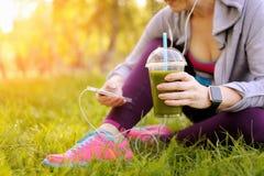 Mujer deportiva que se sienta en hierba en parque Imágenes de archivo libres de regalías