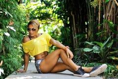 Mujer deportiva que se sienta en un parque verde en verano Fotografía de archivo libre de regalías