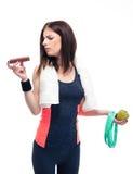 Mujer deportiva que toma la decisión entre la manzana y el chocolate Imagen de archivo libre de regalías
