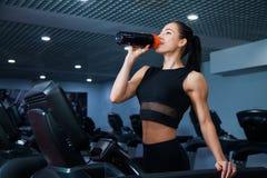 Mujer deportiva sana apta que hace ejercicio cardiio en el agua de la bebida de la rueda de ardilla Foto de archivo libre de regalías