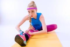 Mujer deportiva seria que estira en la estera del entrenamiento Foto de archivo libre de regalías