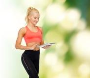 Mujer deportiva sonriente con el ordenador de la PC de la tableta Fotos de archivo