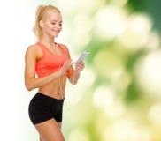 Mujer deportiva sonriente con smartphone y los auriculares Imagenes de archivo