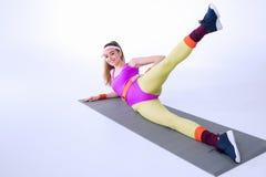 Mujer deportiva sonriente que ejercita en la estera del entrenamiento Imagenes de archivo