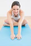 Mujer deportiva sonriente que estira las manos en la estera del ejercicio Foto de archivo