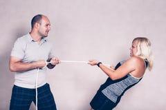 Mujer deportiva y hombre resueltos que tiran de una cuerda Foto de archivo libre de regalías