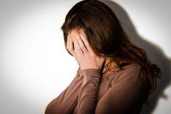 Mujer deprimida con la cabeza en manos Imágenes de archivo libres de regalías