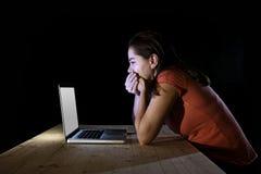Mujer deprimida del trabajador o del estudiante que trabaja con de última hora solo del ordenador en la tensión Foto de archivo libre de regalías