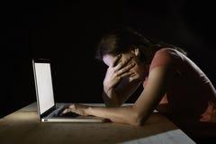 Mujer deprimida del trabajador o del estudiante que trabaja con de última hora solo del ordenador en la tensión Foto de archivo