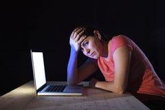 Mujer deprimida del trabajador o del estudiante que trabaja con de última hora solo del ordenador en la tensión Imágenes de archivo libres de regalías