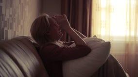 Mujer deprimida en cama muchacha que llora en el sofá montaña aguda almacen de metraje de vídeo