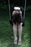 Mujer deprimida en el oscilación Imagenes de archivo