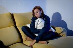 Mujer deprimida joven en el sofá con el amortiguador de la almohada que llora solamente en la tensión fotos de archivo libres de regalías