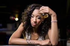 Mujer deprimida que come cerveza en el contador del whisky Imágenes de archivo libres de regalías