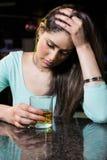 Mujer deprimida que come whisky en el contador de la barra Imagen de archivo libre de regalías