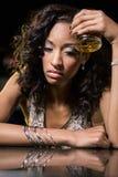 Mujer deprimida que come whisky en el contador de la barra Foto de archivo libre de regalías