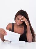 Mujer deprimida que detiene a Bill At Table Imagen de archivo