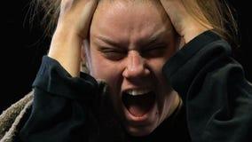 Mujer deprimida que grita llevando a cabo la cabeza con las manos, voces extrañas, psicosis almacen de metraje de vídeo