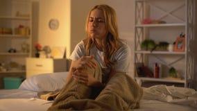 Mujer deprimida que mastica el buñuelo que se sienta en la cama, tensión que come excesivamente, comida malsana almacen de metraje de vídeo