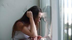 Mujer deprimida que mira hacia fuera la ventana metrajes