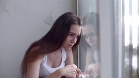 Mujer deprimida que mira hacia fuera la ventana almacen de video