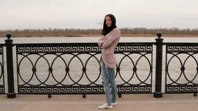 Mujer deprimida que mira la opinión del río del otoño delante de la cerca del metal almacen de video