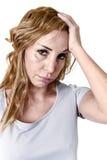 Mujer deprimida que parece desesperada en jaqueca y dolor de cabeza sufridores de la expresión de la cara del dolor Fotos de archivo