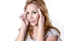 Mujer deprimida que parece desesperada en jaqueca y dolor de cabeza sufridores de la expresión de la cara del dolor Imagenes de archivo