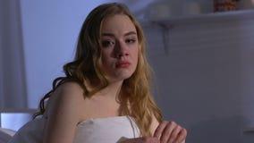 Mujer deprimida que se sienta en cama en la noche y que mira la cámara, problemas de la vida almacen de video