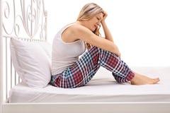 Mujer deprimida que se sienta en una cama y un griterío Fotos de archivo libres de regalías