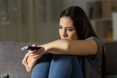 Mujer deprimida que ve la TV en casa Fotos de archivo libres de regalías