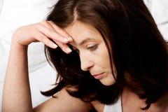 Mujer deprimida triste en cama Foto de archivo libre de regalías