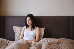 Mujer deprimida triste que piensa en cama en dormitorio de lujo Imagenes de archivo
