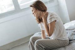 Mujer deprimida triste que sufre de la inflamación del cuello Foto de archivo