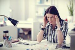 Mujer deprimida triste que tiene un dolor de cabeza Foto de archivo libre de regalías