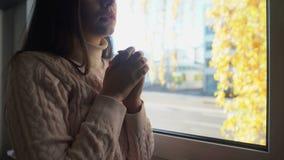 Mujer desamparada joven que mira a través de ventana y que ruega, fe de dios, soledad almacen de metraje de vídeo
