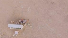 Mujer descalza de los jóvenes que se sienta en el desierto cerca de un piano blanco Visión desde arriba Argumento surrealista Sil metrajes