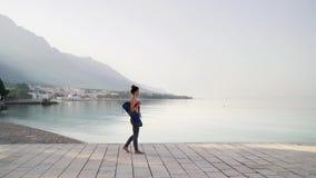 Mujer descalza en ropa de deportes con los paseos de la estera de la yoga en piedra que pavimenta en la playa almacen de video