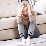 Mujer descalza envejecida centro que se sienta en el piso que abraza sus rodillas, cerca del sofá en casa, su cabeza abajo, aguje Imagen de archivo libre de regalías