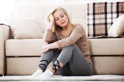 Mujer descalza envejecida centro que se sienta en el piso que abraza sus rodillas, cerca del sofá en casa, su cabeza abajo, aguje Foto de archivo