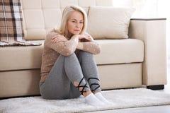 Mujer descalza envejecida centro que se sienta en el piso que abraza sus rodillas, cerca del sofá en casa, su cabeza abajo, aguje Imagen de archivo