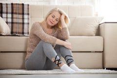 Mujer descalza envejecida centro que se sienta en el piso que abraza sus rodillas, cerca del sofá en casa, su cabeza abajo, aguje Fotos de archivo libres de regalías