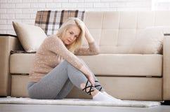 Mujer descalza envejecida centro que se sienta en el piso que abraza sus rodillas, cerca del sofá en casa, su cabeza abajo, aguje Imagenes de archivo
