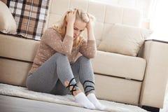 Mujer descalza envejecida centro que se sienta en el piso que abraza sus rodillas, cerca del sofá en casa, su cabeza abajo, aguje Fotos de archivo
