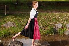 Mujer descalza hermosa en un dirndl Fotos de archivo libres de regalías