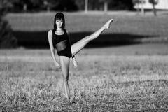 Mujer descalza que ejercita su flexibilidad en un campo Imágenes de archivo libres de regalías