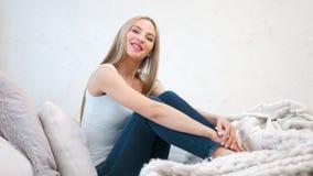 Mujer descalza sonriente atractiva que disfruta de sentarse en el sofá en el tiro lleno casero acogedor almacen de metraje de vídeo