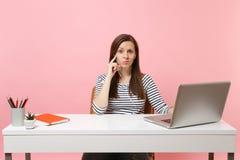 Mujer desconcertada joven con audiolibro de la música de los auriculares que escucha sentarse y trabajar en el escritorio blanco  imágenes de archivo libres de regalías