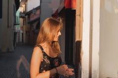 Mujer desconcertada joven que mira la ventana de la tienda en un callejón en ascona foto de archivo libre de regalías