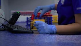 Mujer desconocida del rofessional en uniforme azul y los guantes de goma que ponen el estante para los tubos de ensayo en el refr metrajes